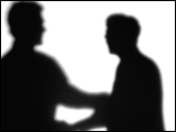 Video Clip - Human figures depicted in black in front of a white background; walking up and shaking hands