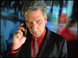 Video Clip - Man talking over the phone with a depiction of a busy street at the back