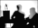 Video Clip - Human figures depicted in black in front of a white background; meeting with a presenter talking