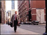 Video Clip - Man with a brown trench coat and a brief case walks down a street and waits at a street light