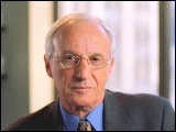 Video Clip - An older man with glasses in business attire looking into the camera