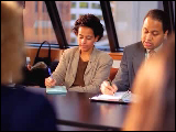 Video Clip - A man and a woman taking notes during a meeting