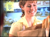 Video Clip - A cashier in a grocery store passing groceries to a customer